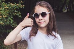 Cute smiling girl in the forest shows finger up, everything is fine.  royalty free stock photo