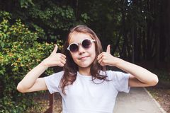 Cute smiling girl in the forest shows two fingers up, everything is fine.  stock photos