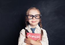 Cute smiling girl with french book in language school classroom. Learning French royalty free stock photos