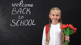 Cute smiling girl holding bunch of tulips near chalkboard welcome back to school. Stock footage stock footage