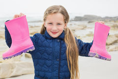 Cute smiling girl holding her wellington boots at beach Royalty Free Stock Image