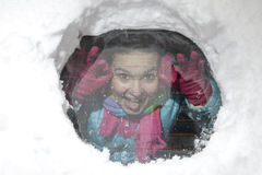 Cute smiling girl joking through a hole in a snowy car window Stock Photo
