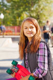 Cute smiling girl with long hair and skateboard Stock Photography