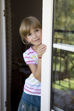 Cute smiling girl looking out balcony door Stock Images