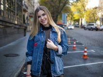 Cute smiling girl with luxurious hair in a denim jacket stands in the parking lot for cars outdoor royalty free stock images