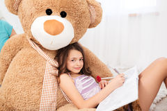 Cute smiling girl lying on big plush bear and drawing. In children room royalty free stock photo