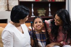 Cute smiling girl with mother and grandmother sitting at home. Cute smiling girl with mother and grandmother sitting together on sofa at home Stock Images