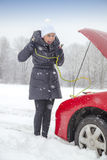 Cute smiling girl needs help on the snowy road Stock Photos