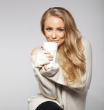 Cute smiling girl in oversized sweater holding cup. Royalty Free Stock Photos