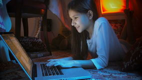 Cute smiling girl in pajamas using laptop in tepee tent at night stock footage