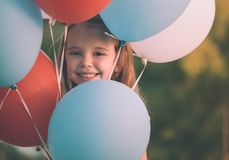 Cute smiling girl peeking through the balloons - Retro look. Cute smiling girl peeking through the balloons against blurry green background - Retro look Royalty Free Stock Photo