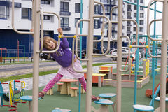 Cute smiling girl on a playground. Against the gray sky Stock Photo