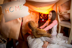 Cute smiling girl playing with teddy bear at house made of blank Stock Image