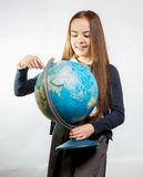 Cute smiling girl pointing at Earth globe against white backgrou Stock Photography
