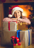 Cute smiling girl posing with Christmas presents at fireplace Stock Photo