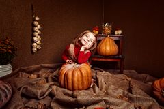 Cute smiling girl with pumpkin. Portrait of adorable smiling girl posing with orange pumpkin in room Royalty Free Stock Photography