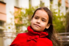 Cute smiling girl in red coat with her hair looking to the side.  stock photos