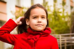 Cute smiling girl in a red coat and tucks her hair.  Stock Image