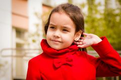 Cute smiling girl in a red coat and tucks her hair.  stock photo
