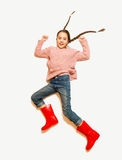 Cute smiling girl in red rubber boots jumping high Royalty Free Stock Images