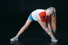 Cute smiling girl in sportswear exercising and looking at camera. Activities for children concept Stock Photos