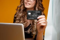 Cute smiling girl using her laptop and credit card for online shopping, nice woman in a black dress holding black card royalty free stock images