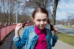 Cute smiling girl in warm sunny weather outside with two pigtails smiling at the camera.  Royalty Free Stock Photo
