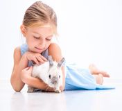 Cute smiling girl with a white rabbit Stock Photos
