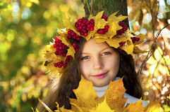 Cute smiling girl in wreath of red viburnum Stock Image