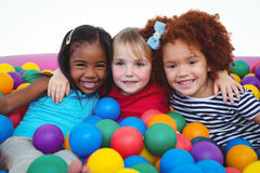 Cute smiling girls in sponge ball pool hugging Royalty Free Stock Photography