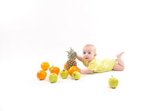 Cute smiling healthy child lies on a white background among frui Royalty Free Stock Photos