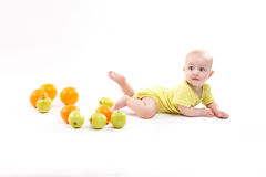 Cute smiling healthy child lies on a white background among frui Royalty Free Stock Photo