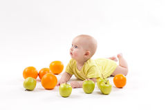 Cute smiling healthy child lies on a white background among frui Stock Photography