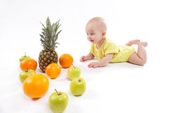 Cute smiling healthy child lies on a white background among frui. Ts. Photo with depth of field Royalty Free Stock Images