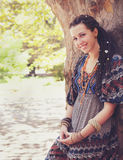 Cute smiling hippie indie style woman with dreadlocks,  dressed in boho style ornamental dress posing outdoor. Empty space for text Royalty Free Stock Photo