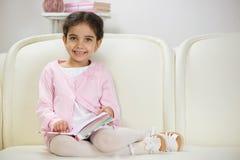 Cute smiling hispanic girl reading book stock photography