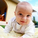 Cute smiling infant baby playing at the yard. Royalty Free Stock Photography
