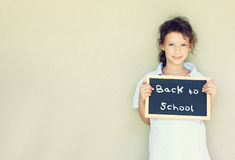 Cute smiling kid (girl) holding blackboard with the phrase back to school against textured wall. room for text. Royalty Free Stock Photo