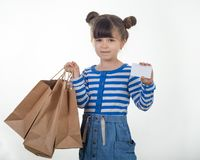 Cute smiling kid holding discount white card and shopping bags in her hands. royalty free stock image