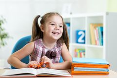 Cute smiling kid reading book in children room. Cute smiling kid girl reading book in children room Royalty Free Stock Photography