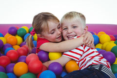 Cute smiling kids in sponge ball pool hugging Royalty Free Stock Photography