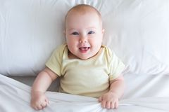 Cute smiling little baby girl lying on the bed under blanket Stock Image