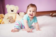 Cute smiling little baby girl sitting on the bed with soft toys Royalty Free Stock Photography