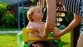Cute smiling little baby girl swinging on a swing in summer day. Slow motion stock footage