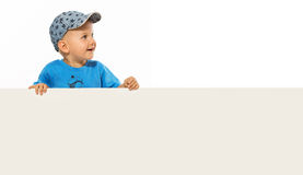 Cute smiling little boy is above on the empty white placard. White bacground Stock Photo