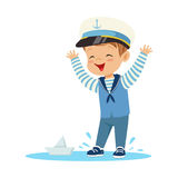 Cute smiling little boy character wearing a sailors costume standing in a puddle playing with paper boat colorful vector Stock Image