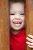 Cute smiling little boy peeking out Stock Image