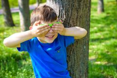 Cute smiling little boy in sunglasses on forest background closing two eye with his hand. stock images