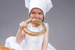 Cute and Smiling Little Caucasian Girl In Cook Uniform Posing With Doughnut Bread Roll Royalty Free Stock Photo