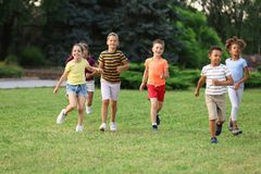 Cute smiling little children playing. In park stock photography